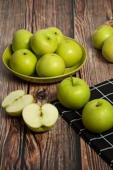 Свежие зеленые яблоки над столом