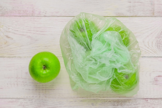 Fresh green apples in plastic bag on wooden table. environmental concept of non-ecological use of plastic