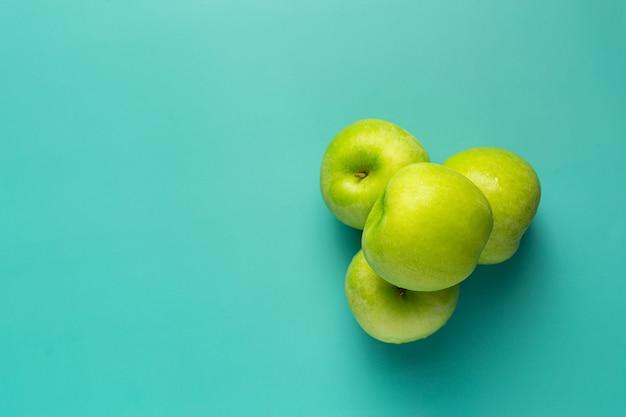 薄緑色の背景に新鮮な青リンゴを置く