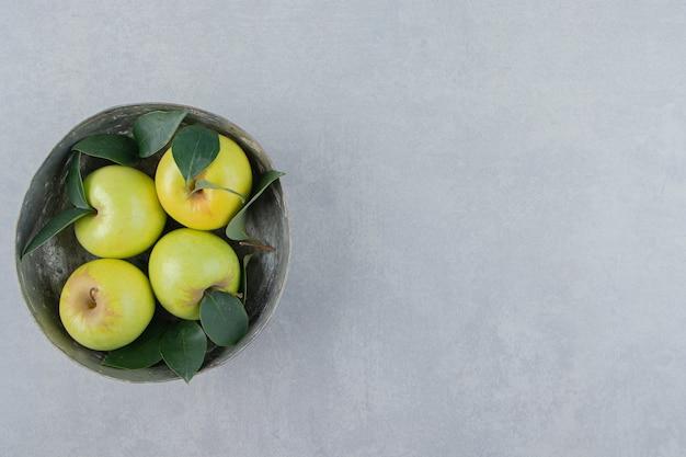 그릇에 잎과 신선한 녹색 사과입니다.