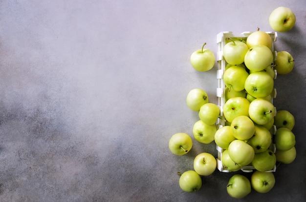 Fresh green apples in wooden box on light grey .