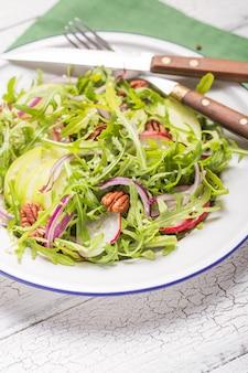 白いボウルに新鮮なルッコラの葉、リンゴ、大根、ピーカンナッツ、木製の素朴な背景にタマネギのルッコラロケットサラダ