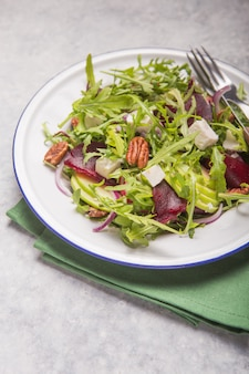 Fresh green arugula leaves on white bowl, rucola rocket salad on  wooden rustic background
