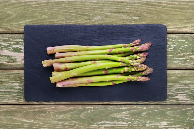 Fresh green asparagus on black slate cutting board on green wooden table top view copy space