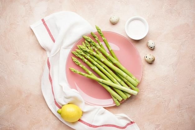 베이지 색 표면에 접시에 신선한 그린 아스파라거스. 플랫 레이