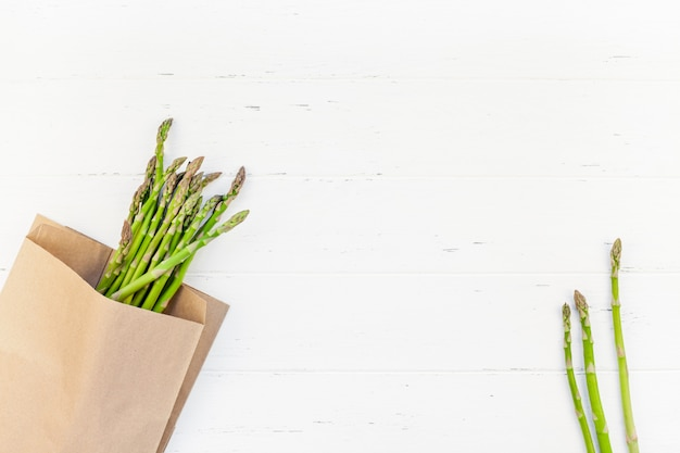 Fresh green asparagus on white wooden surface
