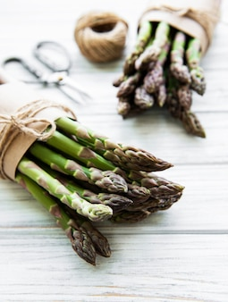 Fresh green asparagus with scissors and thread on old wooden table