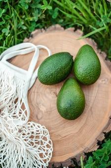둥근 나무 보드에 신선한 녹색 avacado 프레임에 에코 메쉬 쇼핑백