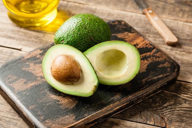 나무 테이블에 신선한 녹색 아보카도와 기름
