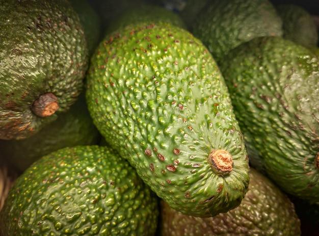 Свежие зеленые авокадо или persea americana готовы к продаже. тропические авокадо фрукты на рынке стойло.