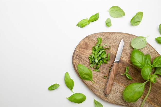 Свежие зеленые травы базилика с ножом на деревянной доске фон травы