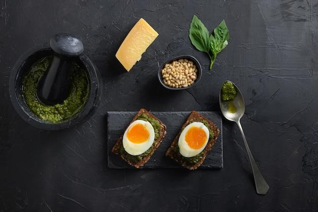 古い素朴な木の卵のパニーニパンにペストを添えて自家製の乳鉢で新鮮な緑のバジルペスト
