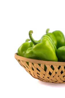 Fresh green bell pepper or capsicum in bamboo basket on a white