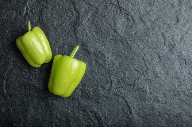 Fresh green bell peppers on black.
