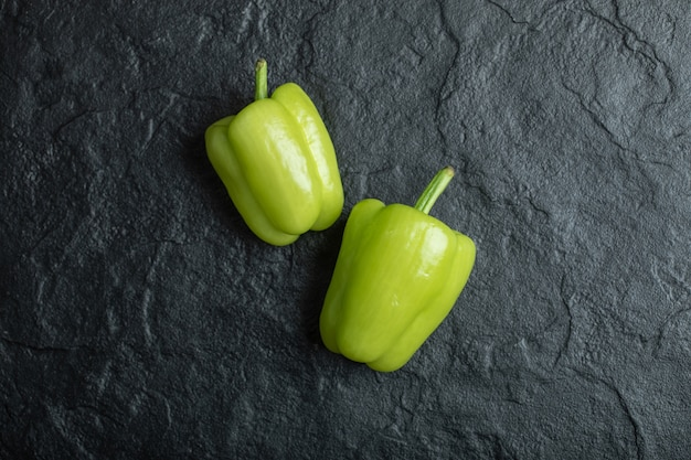 Свежий зеленый перец на черном.