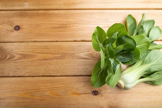 茶色の木製の背景に新鮮な緑の青梗菜またはパックチョイ白菜。
