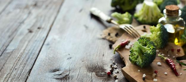 木製のテーブルに新鮮な緑のブロッコリーと野菜