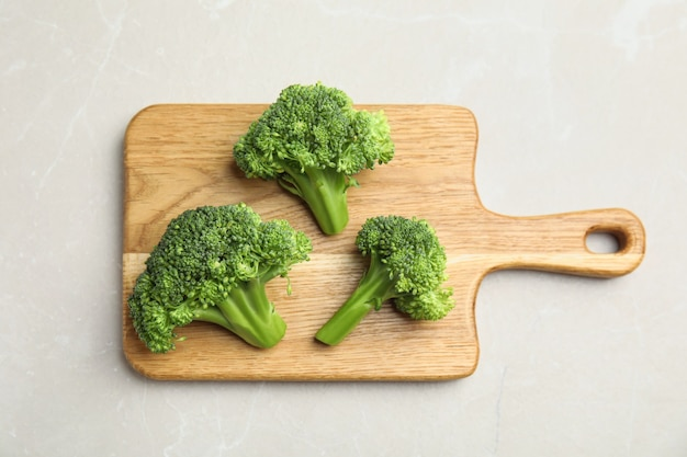 Fresh green broccoli on light marble table, top view