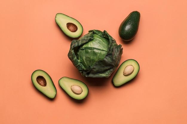 Свежая зеленая капуста с авокадо на цветном оранжевом фоне. концепция здорового питания и витаминов.