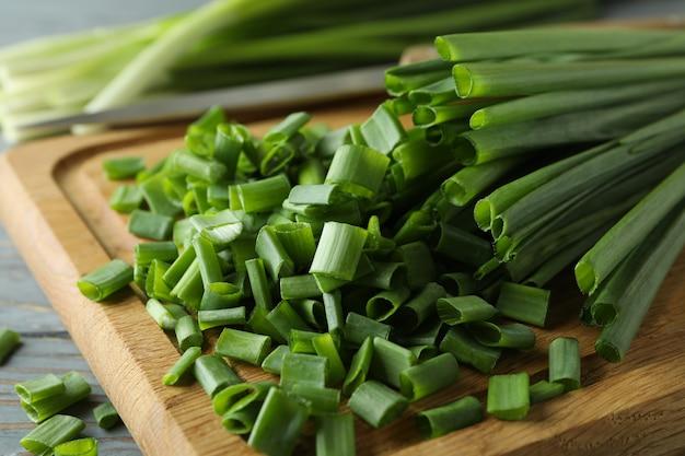 Свежий зеленый нарезанный лук на разделочной доске, крупным планом