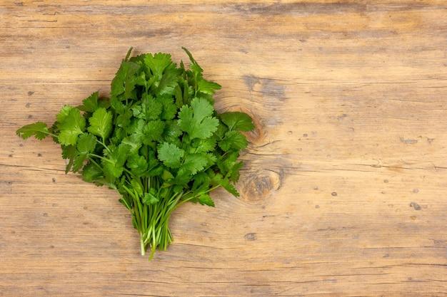 レシピのコピースペースと木製の壁に新鮮な緑のコリアンダーの葉