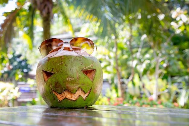 顔が刻まれたハロウィーンのカボチャココナッツの形をした新鮮な緑のココナッツがテーブルの上にあります