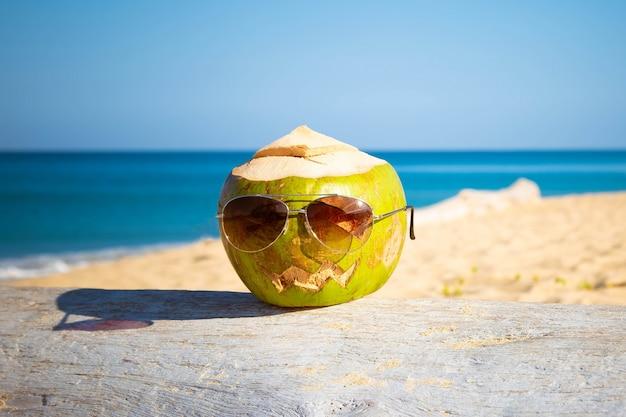 サングラスの新鮮な緑のココナッツは、カボチャのような彫刻が施された顔を持つ木のハロウィーンの嘘のシンボルです