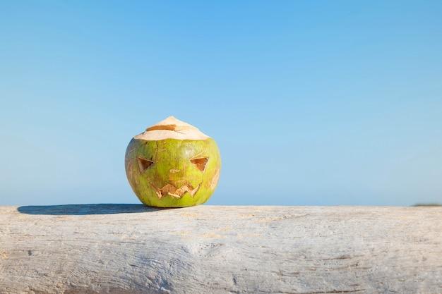 新鮮な緑のココナッツは、カボチャのような刻まれた顔を持つ木の上にハロウィーンの嘘のシンボルです