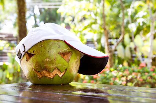 Fresh green coconut on table wearing a white baseball cap halloween symbols carved face of pumpkin