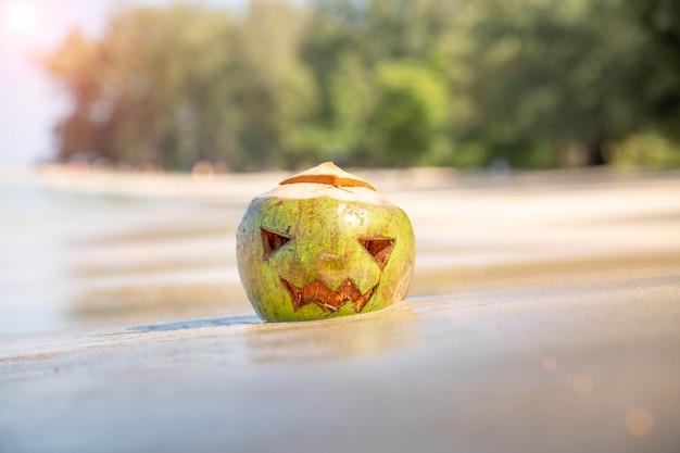 Свежий зеленый кокос с вырезанным лицом, как на хэллоуин, тыква, песчаный пляж, тропический, осенний отдых