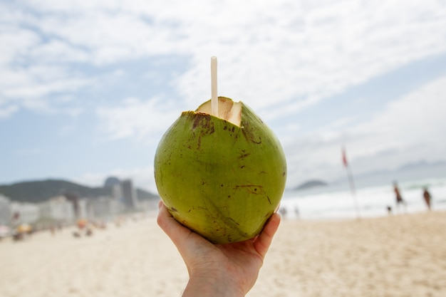 Fresh green coconut with a straw on a beach background.