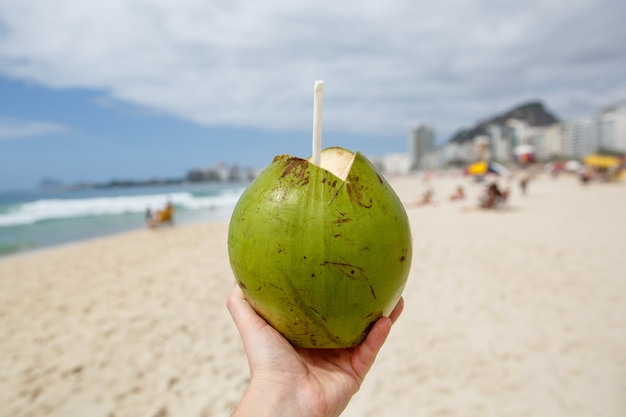 Fresh green coconut with a straw on a beach