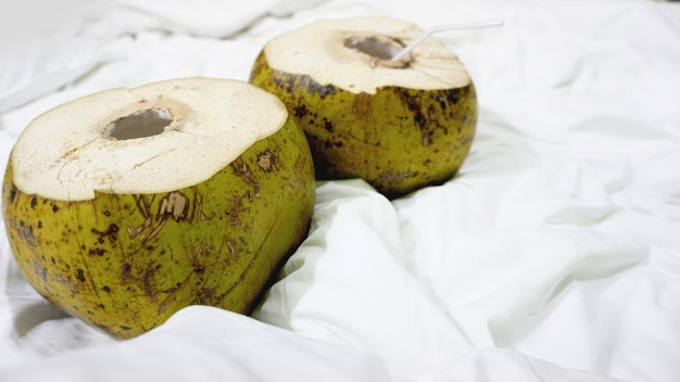 Fresh green coconut with straw ready to drinking on white fabric background