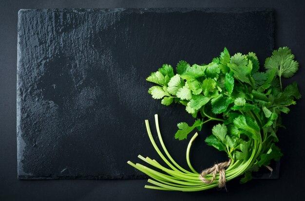 新鮮な緑のコリアンダー、コリアンダーは黒いテーブルの上に残します。セレクティブフォーカス。