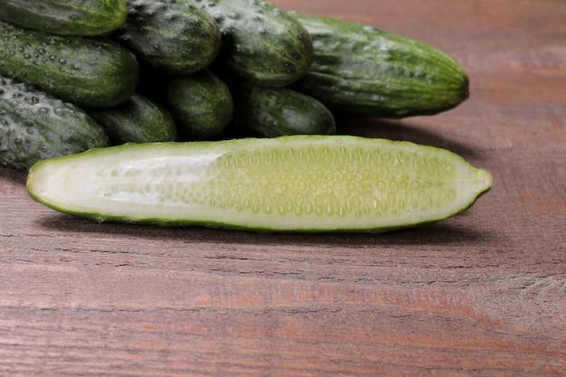 Свежие зеленые огурцы и огурец в разрезе на коричневом деревянном столе. овощи