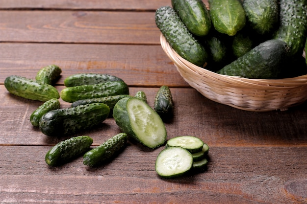 Свежие зеленые огурцы в корзине и кусочки огурцов на коричневом деревянном столе. овощи