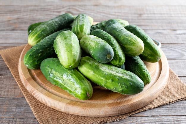 Свежие зеленые огурцы на разделочной доске на деревянном столе. здоровый вегетарианский ингредиент