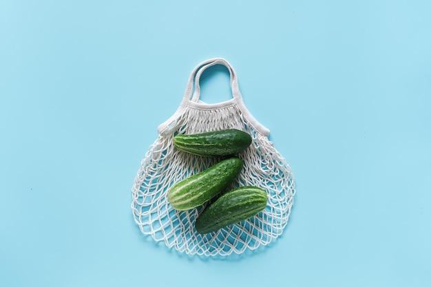 Овощи свежие зеленые огурцы на многоразовой покупки экологически чистой сетчатой сумке на синем фоне