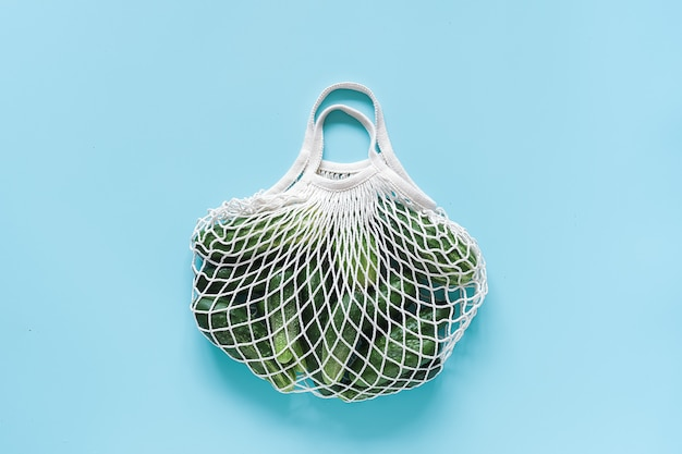 Fresh green cucumbers vegetables in reusable shopping eco-frendly mesh bag on blue background.