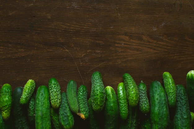 Fresh green cucumbers on wooden background