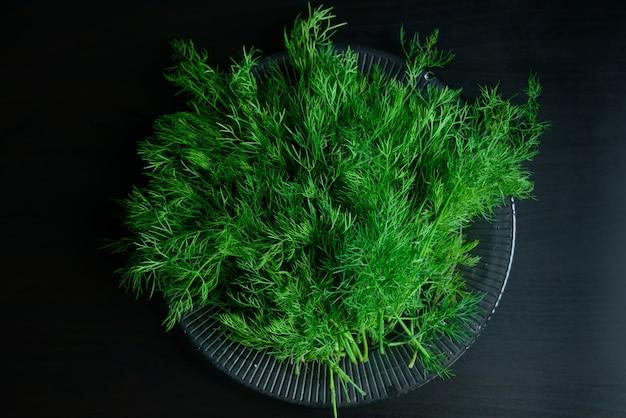 Свежий зеленый укроп для салата или заморозки на черном деревянном столе