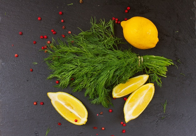 Fresh green dill with red pepper spice and lemons on black board