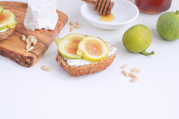 Fresh green figs wooden cutboard wholegrain bread honey goat cheese pine nuts