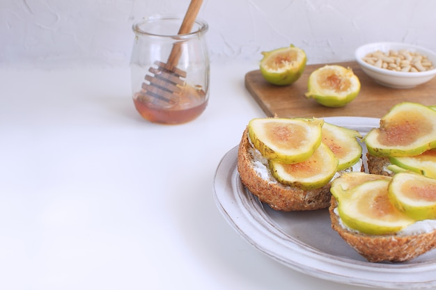 Fresh green figs wooden cutboard wholegrain bread honey goat cheese