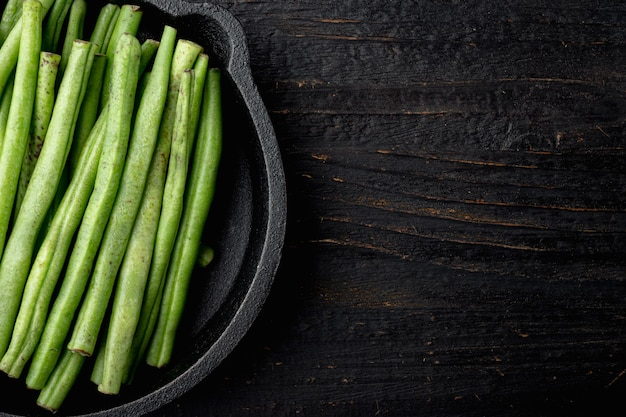 검은 나무 테이블에 주철 팬 프라이팬에 신선한 녹색 프랑스 콩 세트