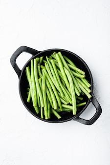 신선한 녹색 프랑스 콩 세트, 튀김 주철 팬, 흰색 돌 배경, 위쪽 전망 플랫 레이, 텍스트 복사 공간