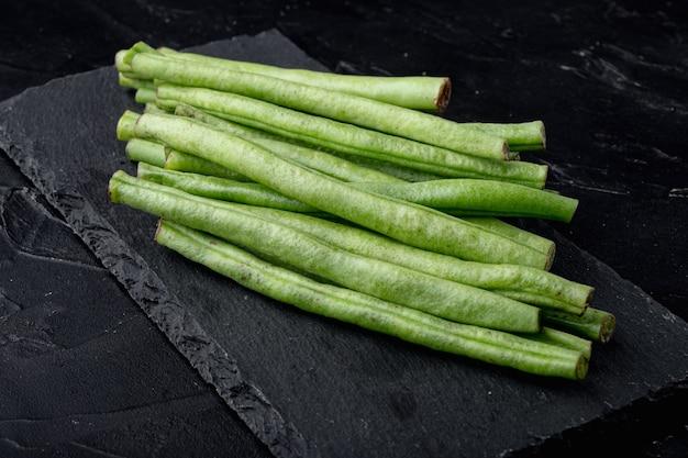 검은 배경에 돌판에 신선한 녹색 프랑스 콩 세트