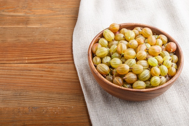 Fresh green gooseberry in wooden bowl on wooden background. side view.