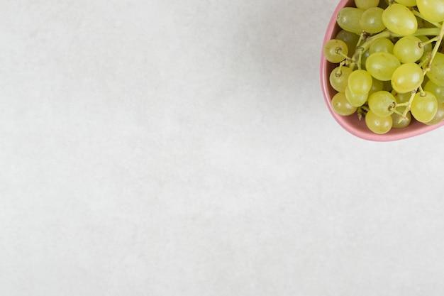 Свежий зеленый виноград в розовой миске