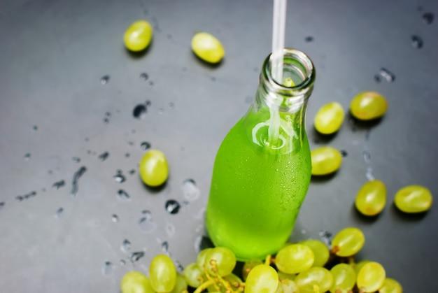 Fresh green grapes juice bottles dark table